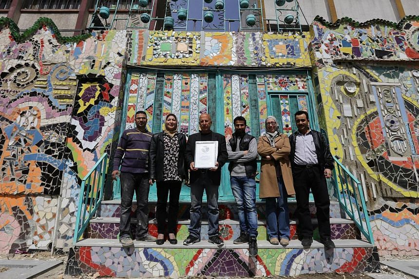 Syrian Moaffak Makhoul and a team of six artists pose with their Guinness World Records award for the largest mural made from recycled material in Damascus's al-Mazzeh neighborhood on March 31, 2014 . -- PHOTO: AFP