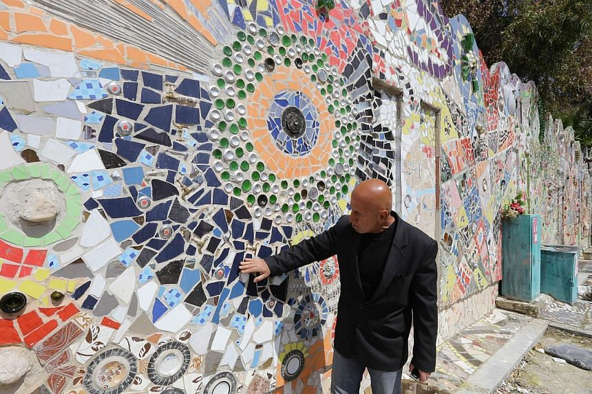 Syrian artist Moaffak Makhoul poses near his decorated wall after it won the Guinness World Records award for the largest mural made from recycled material in Damascus's al-Mazzeh neighborhood on March 31, 2014 . -- PHOTO: AFP