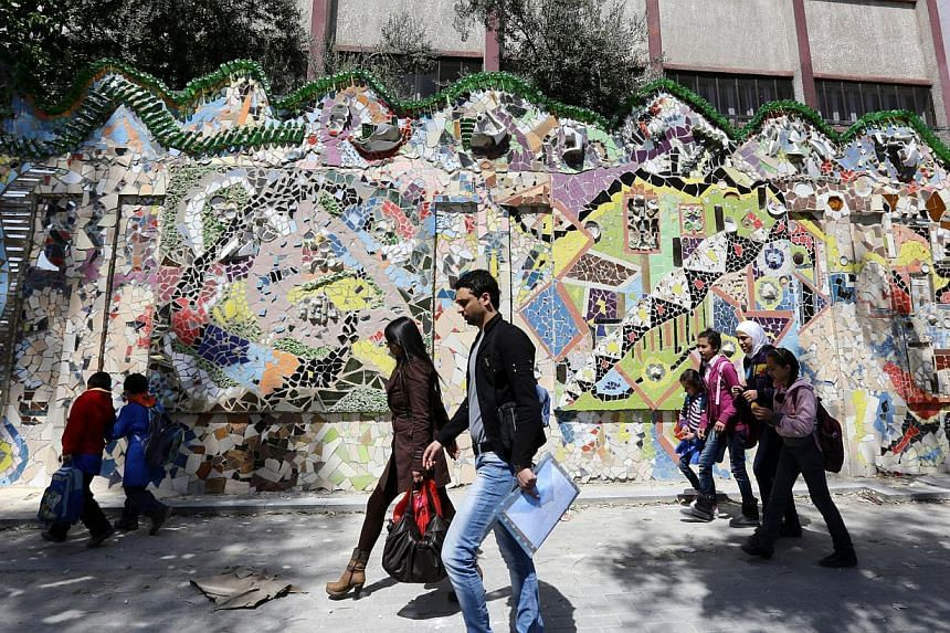 Syrians walk past a decorated wall that won the Guinness World Records award for the largest mural made from recycled material in Damascus's al-Mazzeh neighborhood on March 31, 2014 . -- PHOTO: AFP