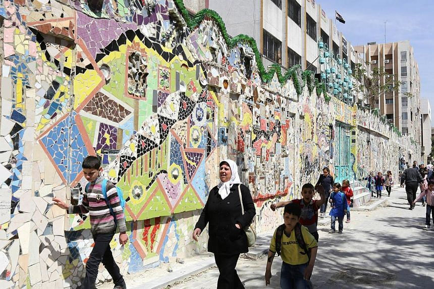 Syrian school children walk past a decorated wall that won the Guinness World Records award for the largest mural made from recycled material in Damascus's al-Mazzeh neighborhood on March 31, 2014 . -- PHOTO: AFP