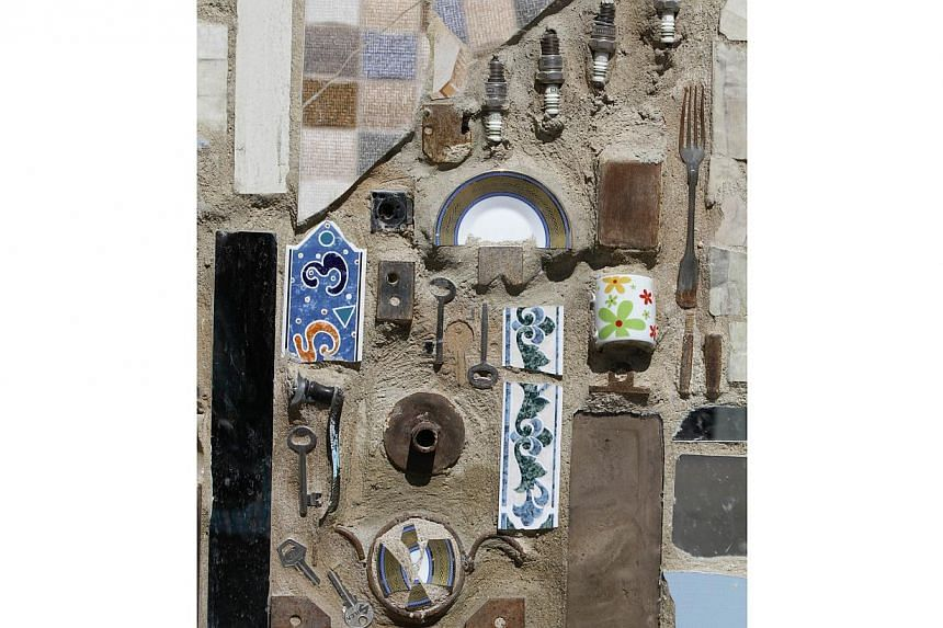 A close up of a decorated wall that won the Guinness World Records award for the largest mural made from recycled material in Damascus's al-Mazzeh neighborhood on March 31, 2014 . -- PHOTO: AFP