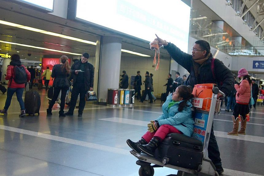 A family walks with a luggage trolley at Beijing's international airport on Jan 9, 2014.The Asia-Pacific region, led by China, will be the main force driving world tourism in the next 10 years, a consultancy survey forecast on Wednesday. -- FIL