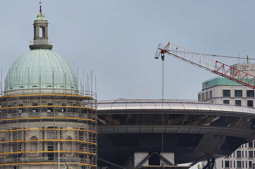The Old Supreme Court Dome (left) being renovated, with the new supreme court in the background (right).The Old Supreme Court, along with City Hall, will become the National Art Gallery in 2015. -- ST FILE PHOTO: TED CHEN