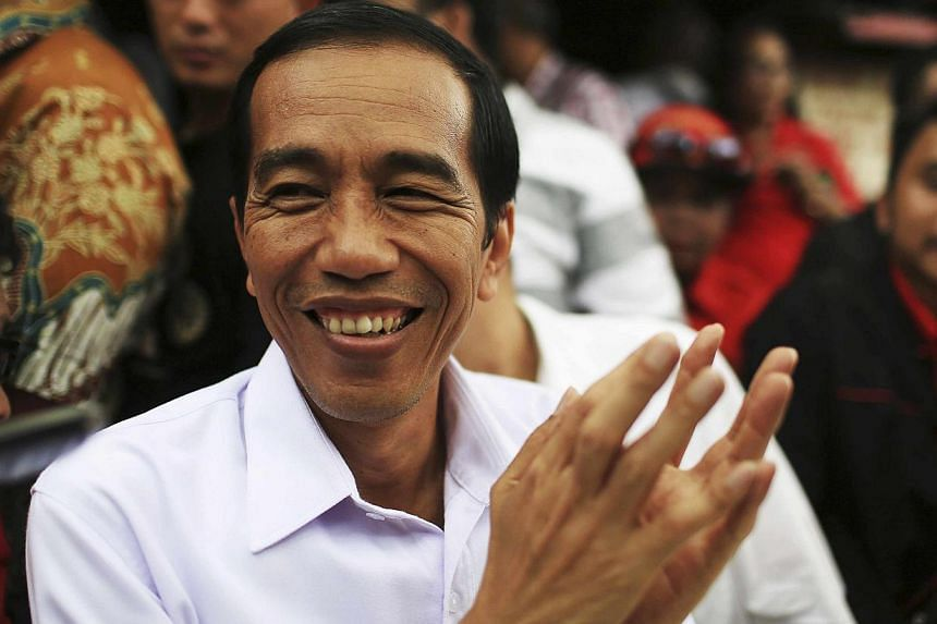 Jakarta governor and presidential candidate Joko Widodo, of the Indonesian Democratic Party of Struggle (PDI-P), reacts during a party campaign at Cengkareng soccer field in Jakarta on March 16, 2014. -- FILE PHOTO: REUTERS