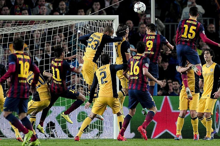Barcelona's Chilean forward Alexis Sanchez (9) jumps for a header during the Champions League quarterfinal first leg football match against Atletico Madrid at the Camp Nou stadium in Barcelona on April 1, 2014. -- PHOTO: AFP
