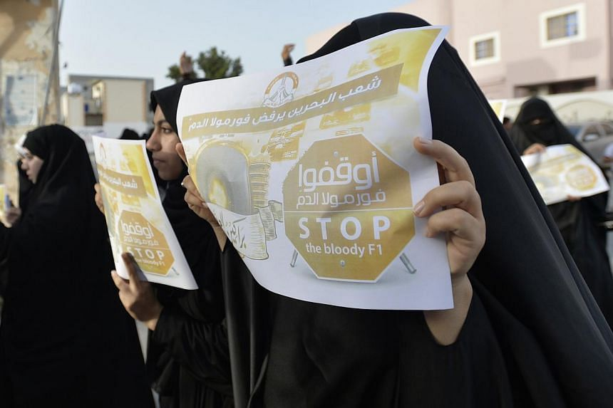 Anti-government protesters hold anti-F1 posters as they march on streets of the village of Diraz, west of Manama, on April 1, 2014. -- PHOTO: REUTERS