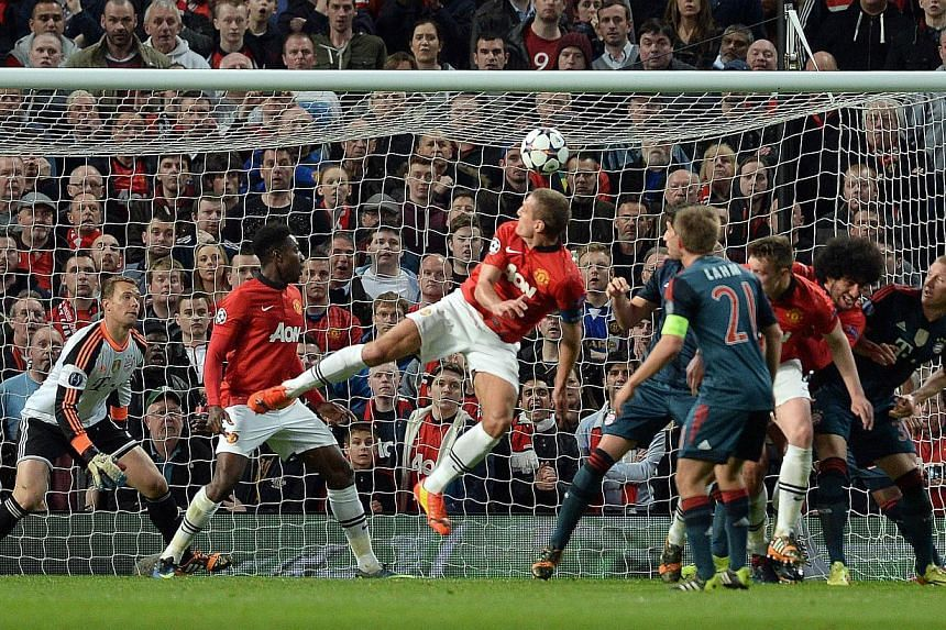 Manchester United's Serbian defender Nemanja Vidic (centre) scores the opening goal during the UEFA Champions League quarter-final first leg football match between Manchester United and Bayern Munich at Old Trafford in Manchester on April 1, 2014. --