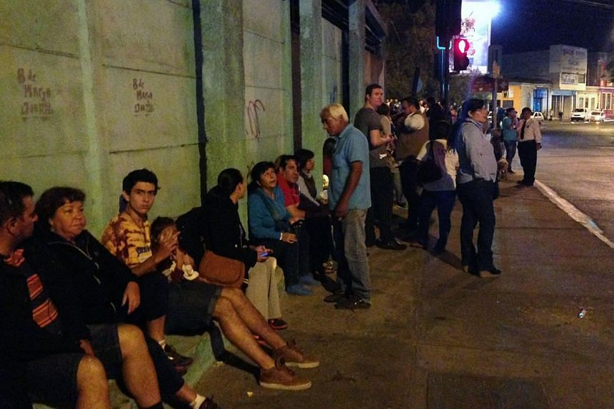 People sitting on the street after a powerful 8.2-magnitude earthquake hit off Chile's Pacific coast, in Antofagasta on April 1, 2014.  -- PHOTO: AFP