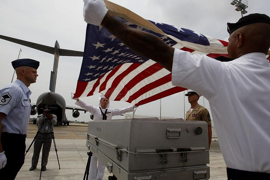 United States personnel prepare a coffin at the Phnom Penh International Airport during a repatriation ceremony, on April 2, 2014. Remains believed to be those of three American servicemen killed in Cambodia more than four decades ago during the Viet