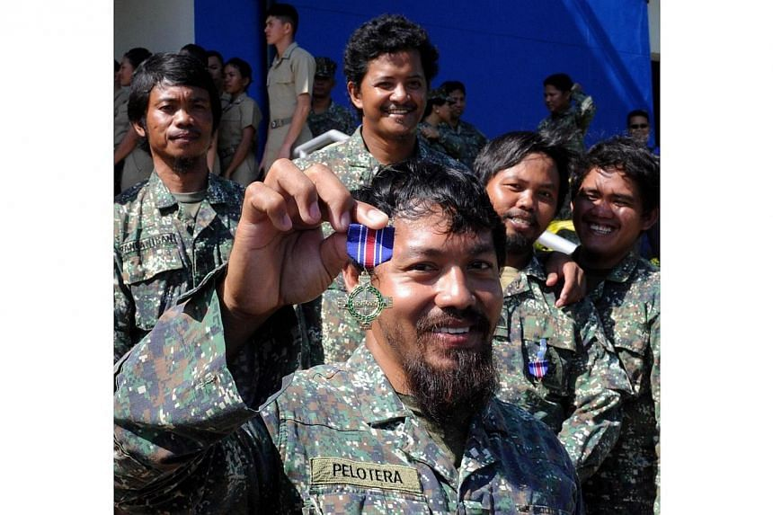 In this photo taken on March 31, 2014, Philippine Marine Lieutenant First Class Mike Pelotera shows his bronze cross medals he received along with eight colleagues after a five-month mission manning the Philippines' remote outpost on the Second Thoma