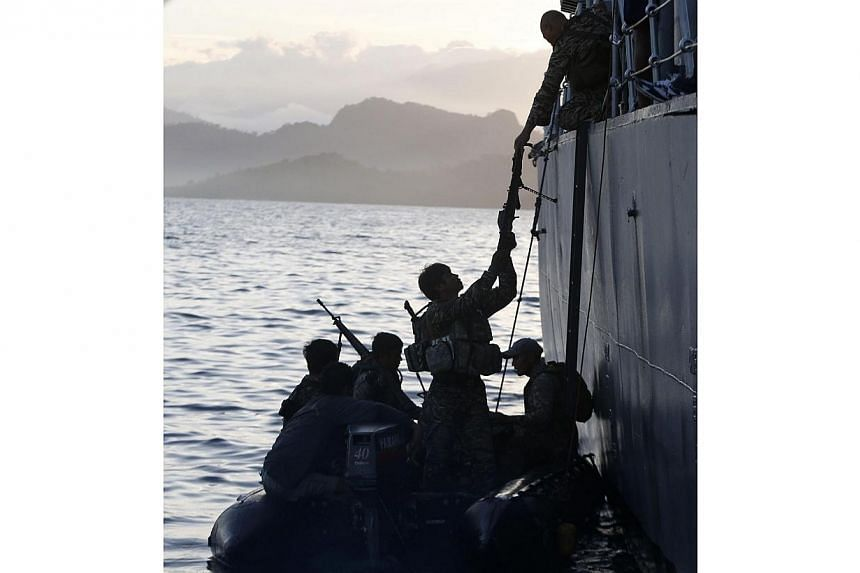 Members of the Philippine marines are transferred on a rubber boat from a patrol ship after conducting a mission at the disputed Second Thomas Shoal, part of the Spratly Islands in the South China Sea, as they return to a naval forces camp in Palawan