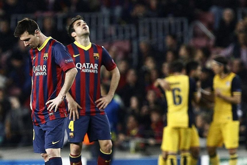 Barcelona's Argentinian forward Lionel Messi (left) and Barcelona's midfielder Cesc Fabregas react after Atletico Madrid's Brazilian midfielder Diego scored a goal during the Uefa Champions League quarterfinal first leg football match. Barcelona have