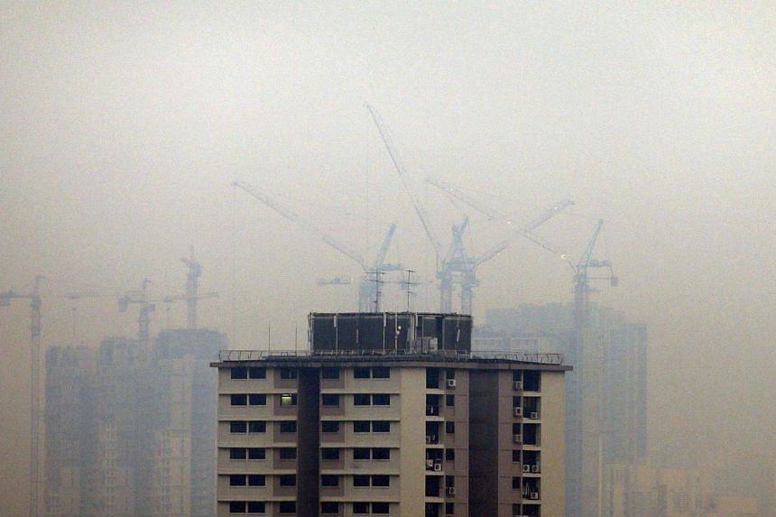 Smoke haze obscures an apartment building under construction in Singapore on March 13, 2014. A meeting on Tuesday, April 2, 2014, between Singapore, Brunei, Thailand, Malaysia and Indonesia delegates to tackle the haze problem has yielded only i