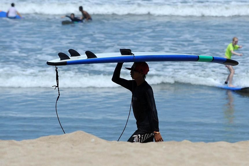 A surfer carries his surfboard on Kuta beach in Denpasar on Indonesia's resort island of Bali on March 10, 2014. Indonesia warned Wednesday, April 2, 2014, that it could be hit by a small tsunami generated by an 8.2-magnitude earthquake that str