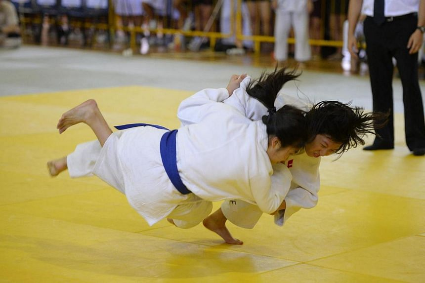 Josephine Wanandi (facing), 16, of Nanyang Girls High (NYGH) and Low Jia Qi, 16, of Raffles Girls School (RGS) pictured during the Girls 'B' Division judo final on April 2, 2014.Nanyang Girls' High School (NYGH) and Hwa Chong Institution (HCI)