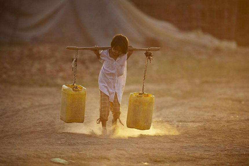 File picture of a child carrying water home through a brick factory on the outskirts of Yangon. A new report by the World Bank said the region lags significantly in its population's access to water supplies, power grids and roads. -- FILE PHOTO: AFP