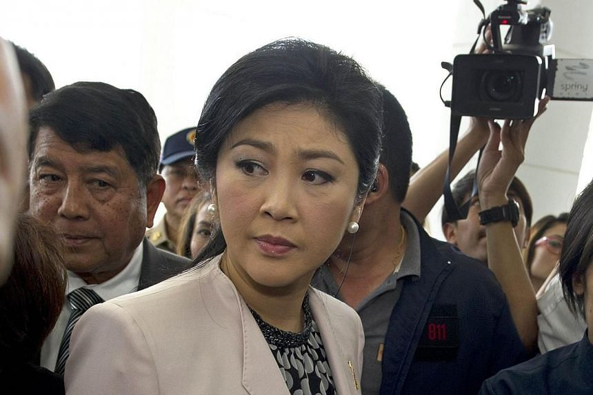 Thai Prime Minister Yingluck Shinawatra (centre) arrives at the National Anti-Corruption Commission (NACC) in Nonthaburi province on March 31, 2014. -- FILE PHOTO: AFP