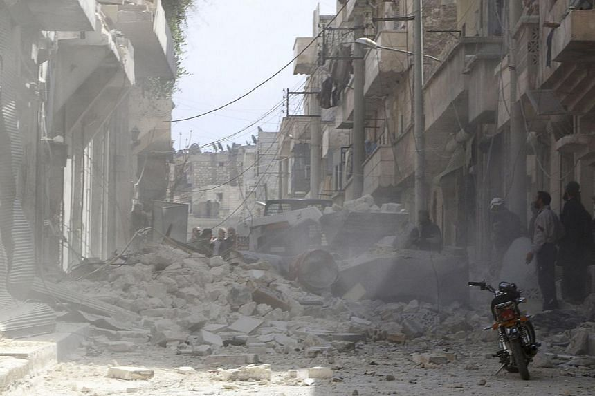 People stand at a site hit by what activists said was an air raid by forces loyal to Syrian President Bashar al-Assad, in the Karam Al-Beik area of Aleppo on April 1, 2014. -- PHOTO: AFP