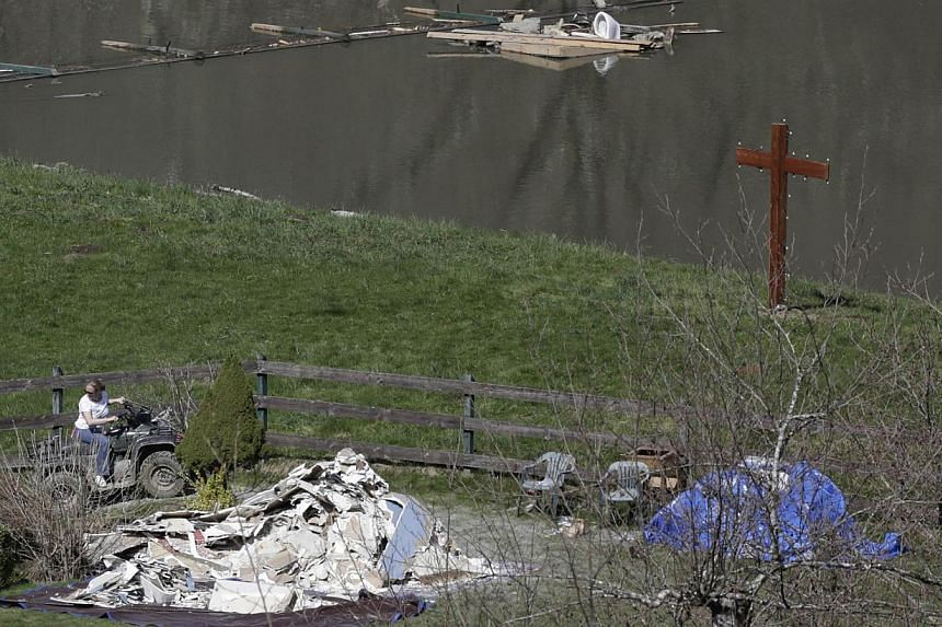 A resident rides an ATV near floodwaters as search work continues in the mud and debris from a massive mudslide that struck Oso near Darrington, Washington on April 1, 2014. -- PHOTO: REUTERS