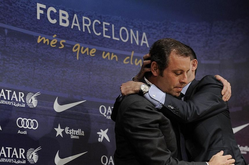 Barcelona's football club president Sandro Rosell (left) is hugged by club vice president Josep Maria Bartomeu during a press conference to announce his resignation following an extraordinary board meeting at the club offices in Barcelona on January