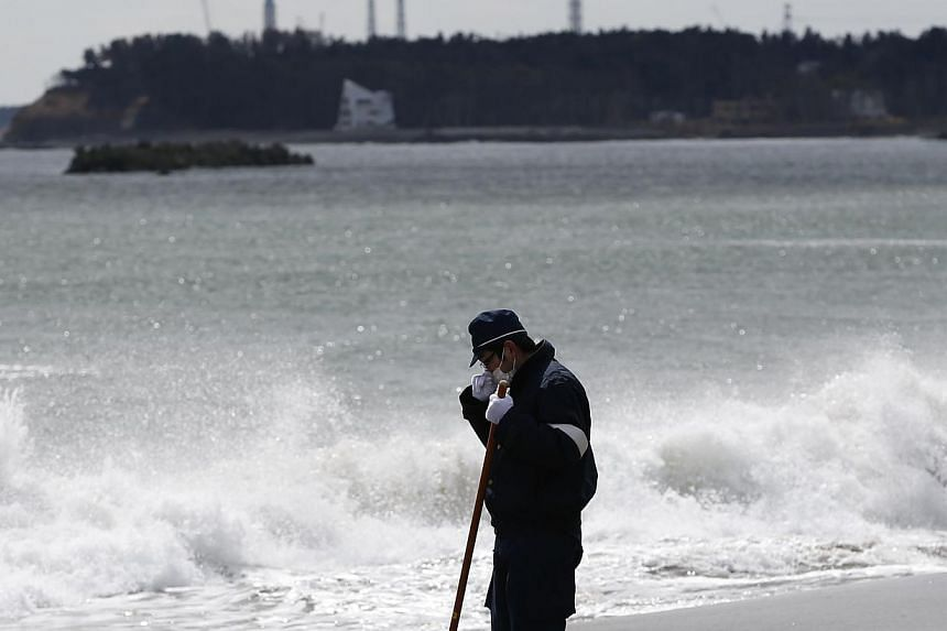 File photo of a police officer searching for missing people in the wake of the 2011 earthquake and tsunami along the coast side. The Tokyo Electric Power Co's (TEPCO) tsunami-crippled Fukushima Daiichi nuclear power plant can be seen in the backgroun