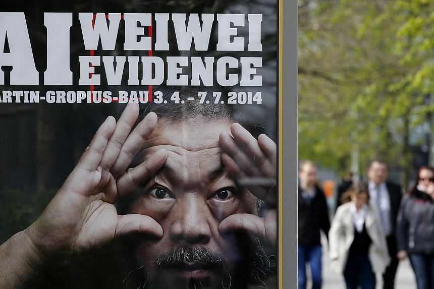 People walk beside an advertising poster for the exhibition Evidence by Chinese artist Ai Weiwei at the Martin-Gropius Bau in Berlin on April 2, 2014. -- PHOTO: REUTERS