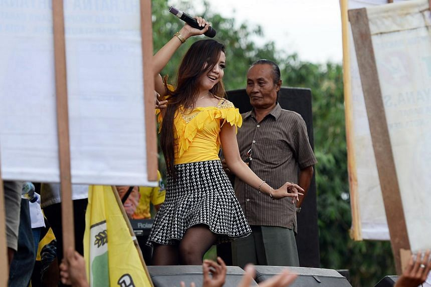 A dangdut singer performing on stage at a Golkar party rally in Depok, West Java, on March 23, 2014. -- SPH PHOTO: RAJ NADARAJAN
