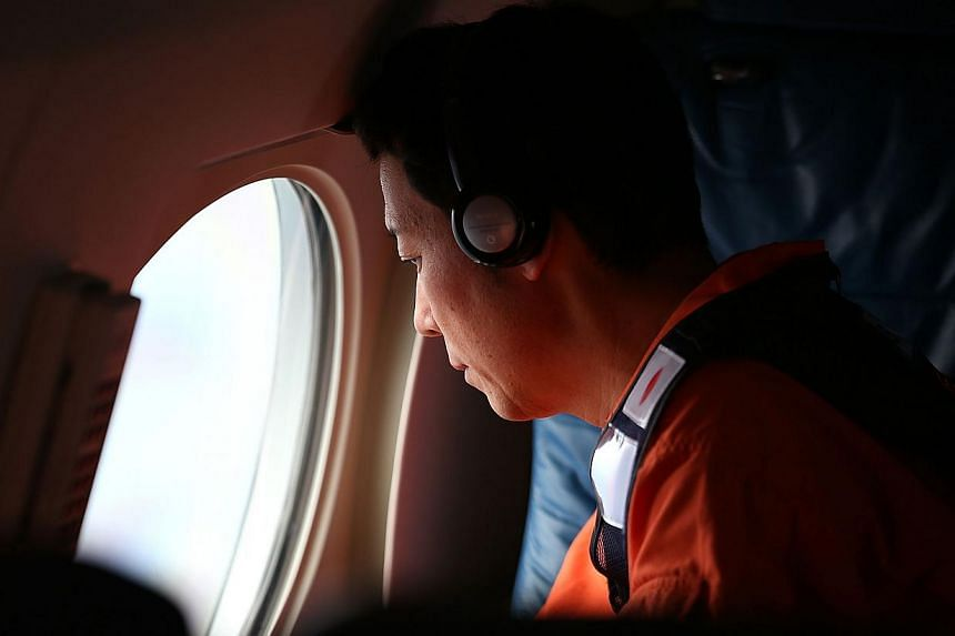 Masaki Sunako of the Japan Coast Guard keeps watch for debris on board the Japan Coast Guard Gulfstream V aircraft whilst in the search zone for debris from Malaysia Airlines flight MH370 on April 1, 2014. -- FILE PHOTO: AFP