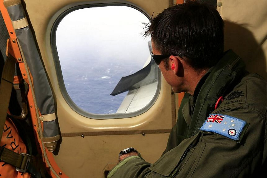 A Flight Engineer from the Royal Australian Air Force looking out of an observation window aboard an RAAF AP-3C Orion maritime patrol aircraft as they continue searching in the southern Indian Ocean for the missing Malaysian Airlines flight MH370 on