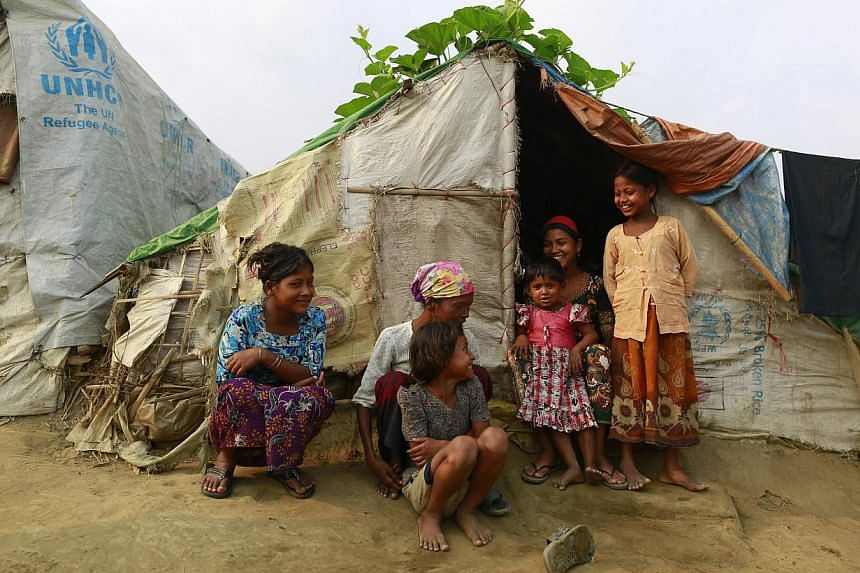 A family in front of their temporary shelter at a Rohingya refugee camp in Sittwe, Myanmar, on April 2, 2014. -- PHOTO: REUTERS