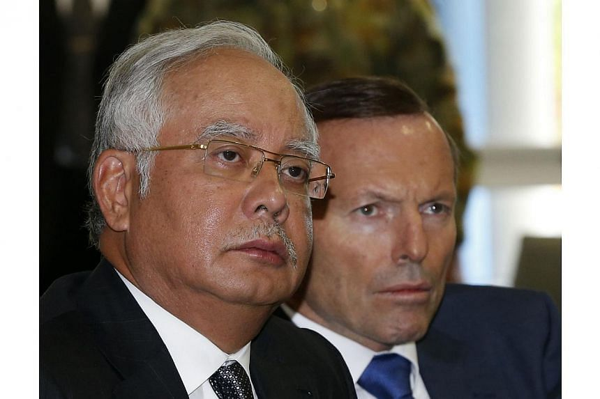 Malaysia's Prime Minister Najib Razak (left) and Australia's Prime Minister Tony Abbott at a briefing on the search for Malaysia Airlines flight MH370 at RAAF Base Pearce near Perth on April 3, 2014. -- PHOTO: REUTERS