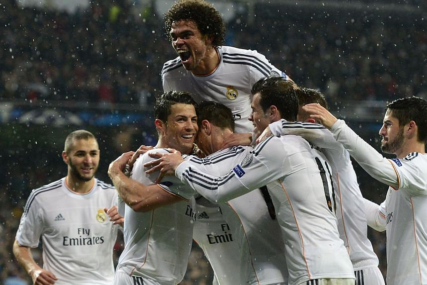 Real Madrid's Portuguese forward Cristiano Ronaldo (left) celebrates with teammates after scoring during the UEFA Champions League quarterfinal first leg football match Real Madrid FC vs Borussia Dortmund at the Santiago Bernabeu stadium in Madrid on