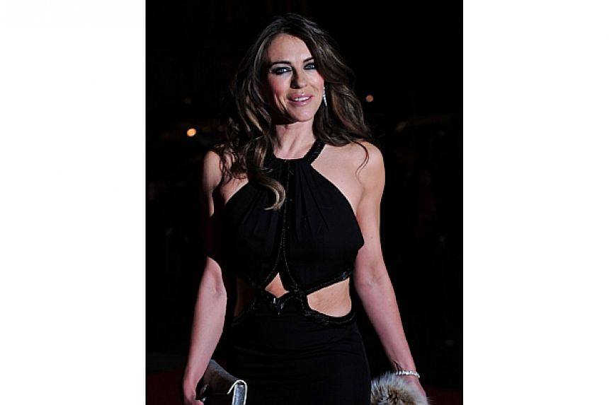 Actress Elizabeth Hurley in a black dress by Roberto Cavalli at the opening of the exhibition. She shot to fame wearing a dress by another Italian fashion house, Versace, at the premiere of Four Weddings And A Funeral (1994).-- PHOTO: AFP