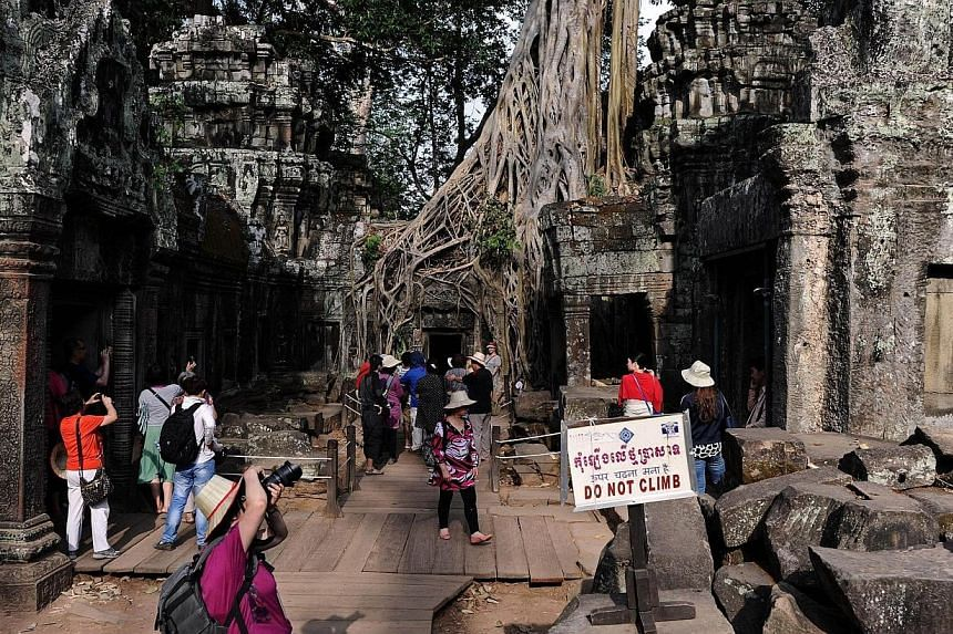 This picture taken on April 2, 2014 shows tourists visiting the Ta Phrom temple, part of the Angkor architectural complex in north-western Cambodia. -- PHOTO: AFP