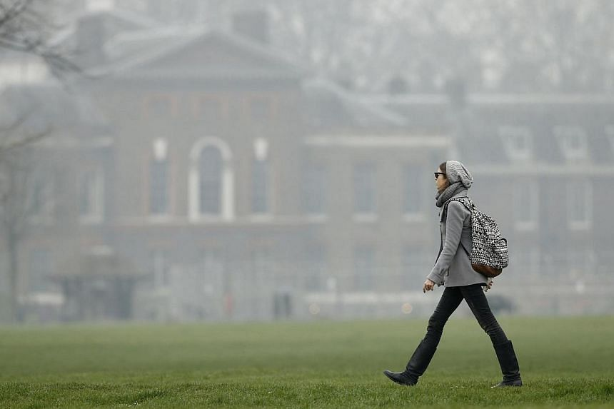 A woman strolls through Kensington Gardens as smog surrounds Kensington Palace in central London on Thursday, April 3, 2014.British Prime Minister David Cameron abandoned his normal early morning run on Thursday because of high pollution levels