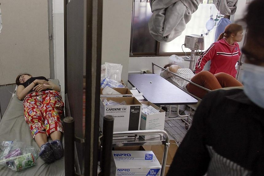 Garment workers recover at a hospital after fainting at a factory in Phnom Penh on Thursday, April 3, 2014. Scores of garment workers have fallen sick at factories in Cambodia including two that produce clothing for sportswear giants Puma SE and