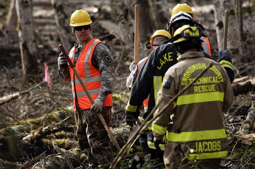 Workers walking through mud and debris as search work continues where a massive mudslide struck Oso near Darrington, Washington, on April 2, 2014. -- PHOTO: REUTERS