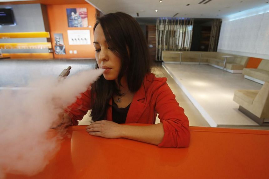 """Enthusiast Brandy Tseu uses an electronic cigarette at The Vapor Spot vapor bar in Los Angeles, California March 4, 2014. The Los Angeles City Council voted unanimously on Tuesday to ban the use of electronic cigarettes, popularly known as """"vaping,"""""""