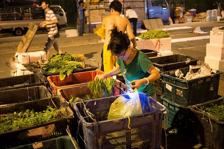 A customer choosing vegetables at a stall. Produce must be bought in bulk, which means at least 1kg, at the wholesale market. -- ST PHOTOS: LIM SIN THAI