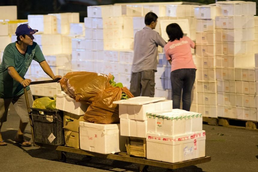 A worker with a load of vegetables to be transferred to a waiting buyer's lorry. Vendors will open up boxes of produce for customers to check if needed. -- ST PHOTOS: LIM SIN THAI