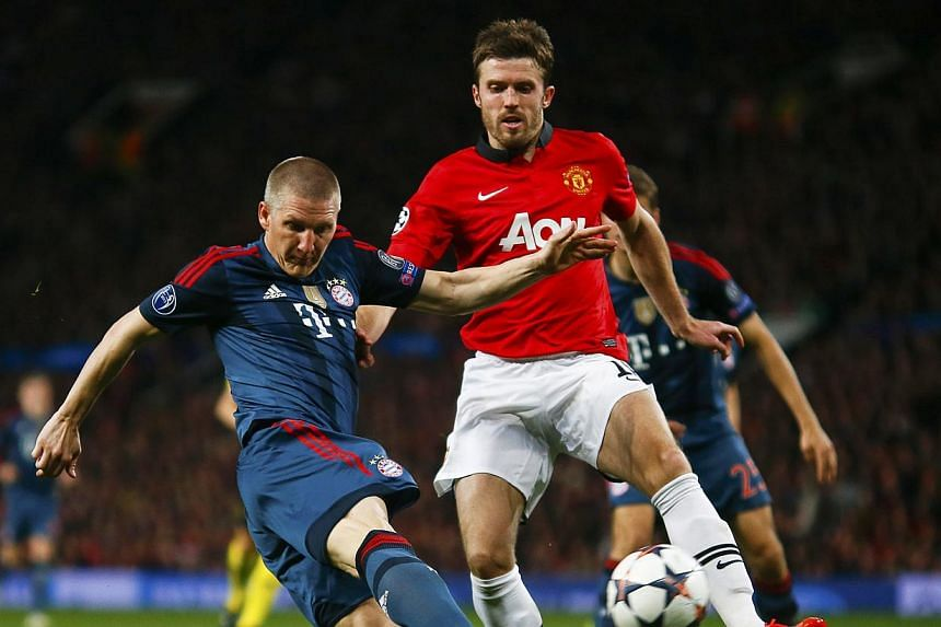 Bayern Munich's Bastian Schweinsteiger (left) challenges Manchester United's Michael Carrick during their Champions League quarter-final first leg soccer match at Old Trafford in Manchester on April 1, 2014. -- PHOTO: REUTERS