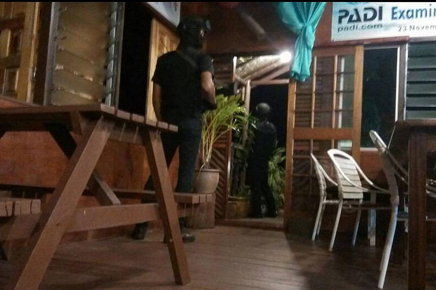 Armed men are seen near a door of a hotel in Sabah on April 2, 2014. A Chinese tourist and a Philippine hotel worker were abducted by armed men at Singamata Reef Resort in Malaysia's eastern state of Sabah. The two abducted women were at the diving r
