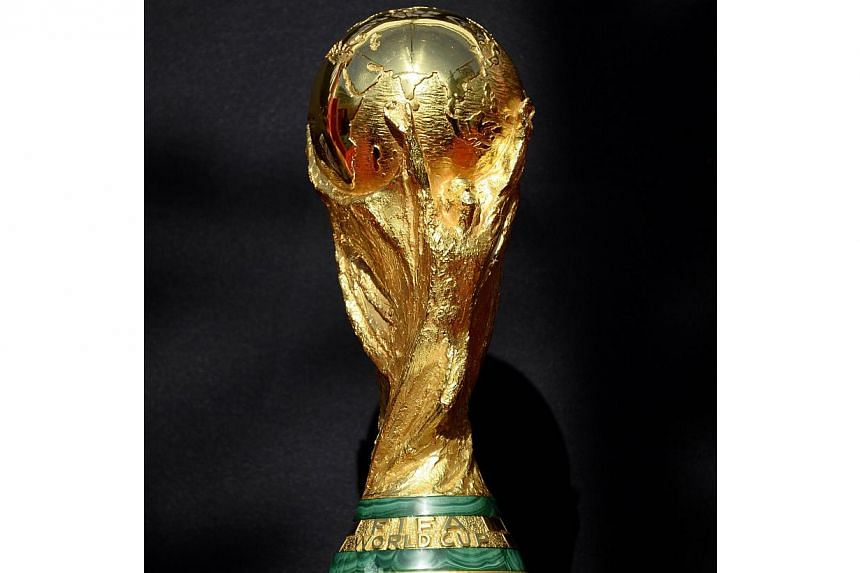 The FIFA World Cup trophy is seen during the FIFA World Cup Trophy Tour on March 9, 2014, outside the Hotel de Ville in Paris. Football fans here can start signing up for their Fifa World Cup 2014 viewing packages after SingTel launched the sales on