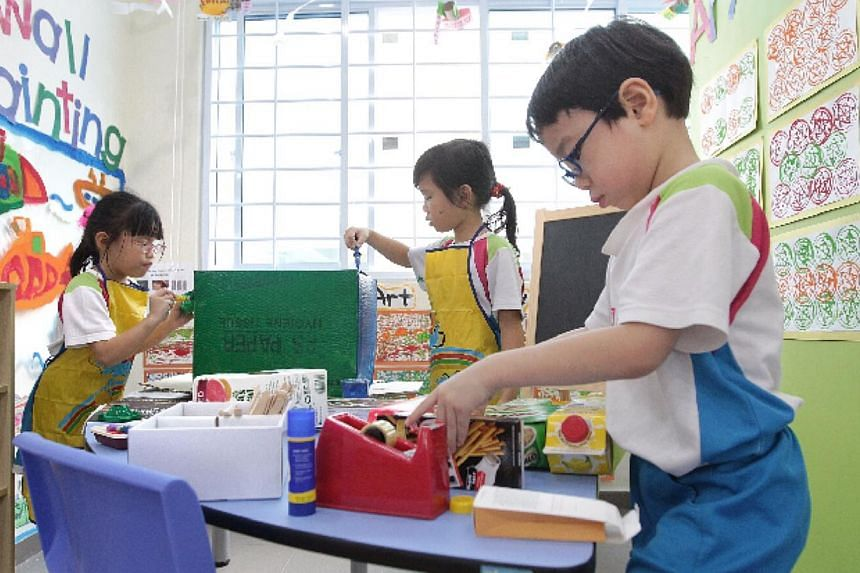 (From left) Six-year-olds Shayne Chin, Charlize Chin, and Brandon Ng, from MY World @ Simei, play at the art corner. -- PHOTO: NEO XIAOBIN