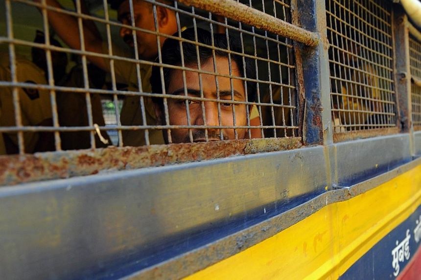 Double gang-rape convict Mohammed Salim Ansari looks out from a police van as he is taken to court in Mumbai on April 4, 2014. -- PHOTO: AFP