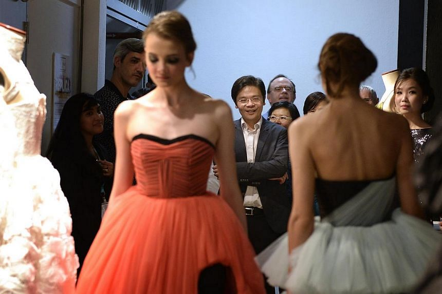 Models wearing clothes made by Lasalle students based on classic designs by famous designers, walk down the a corridor at the new Lasalle Winstedt Campus during the official opening. Minister Lawrence Wong (middle) graced the event as guest-of-honour