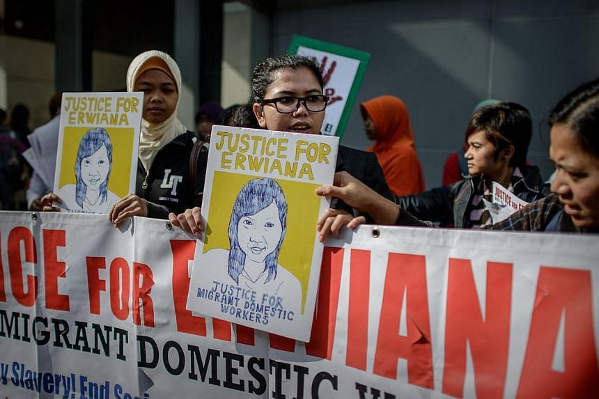 Members of support groups for Indonesian domestic helper Erwiana Sulistyaningsih protest outside a court of justice during the trial of Sulistyaningsih's employer who is charged with causing her grievous bodily harm, in Hong Kong on March 25, 2014. M