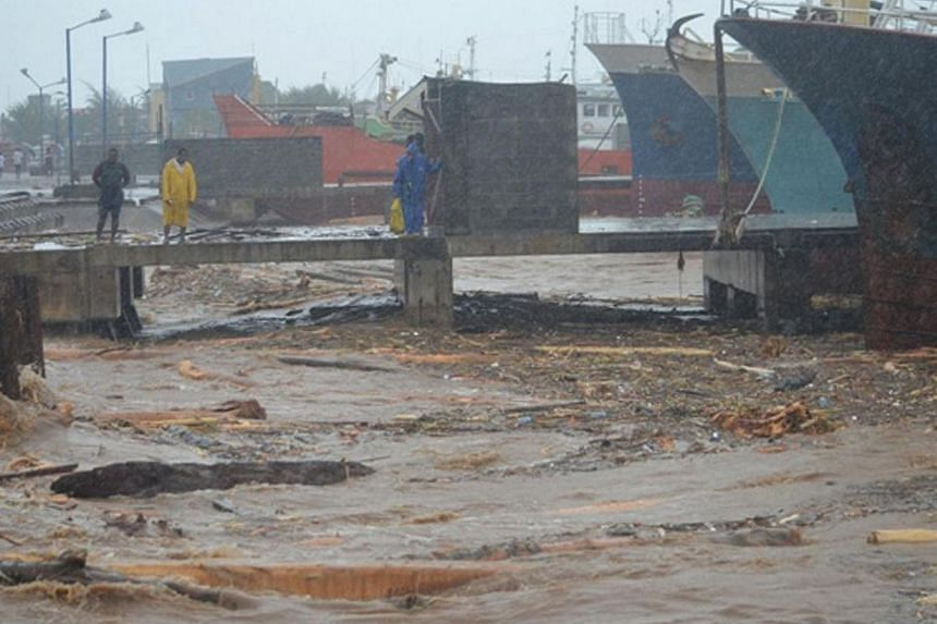 People walk past water clogged with debris at a port in the Solomon Islands' capital Honiara after flooding on Friday, April 4, 2014.A strong 6.0-magnitude earthquake struck the Solomon Islands on Friday, the US Geological Survey (USGS) said, b