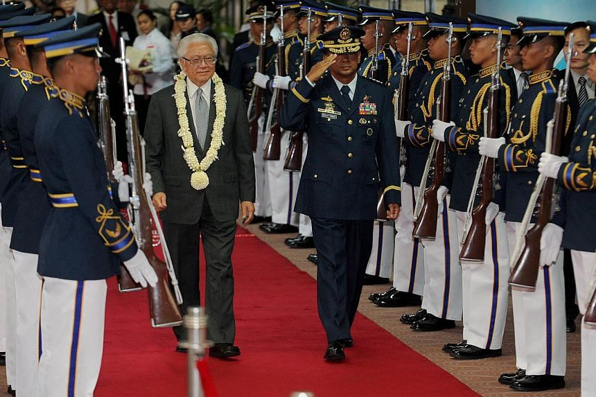Singapore President Tony Tan Keng Yam with Philippine Air Force Chief, Lieutenant General Lauro Catalino Dela Cruz on his arrival at the airport on his first state visit to Manila on April 2, 2014. -- FILE PHOTO: AFP
