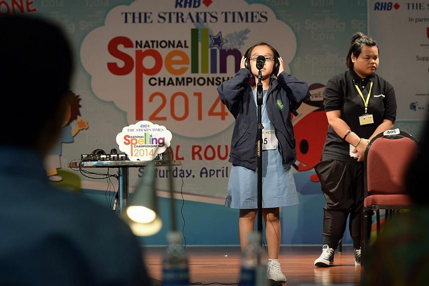 Nicole Lim Hsing Yi, stretches to reach the microphone at the ST-MOE National Spelling Championships zonal rounds (South Zone). -- ST PHOTO: NG SOR LUAN